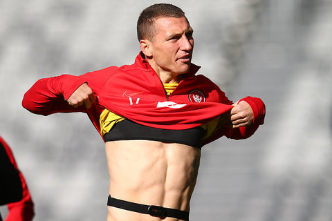 Mitchell Duke lifts football shirt showing abs and body wearing heart rate monitor