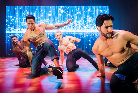 Four topless male dancers slide on stage towards cam