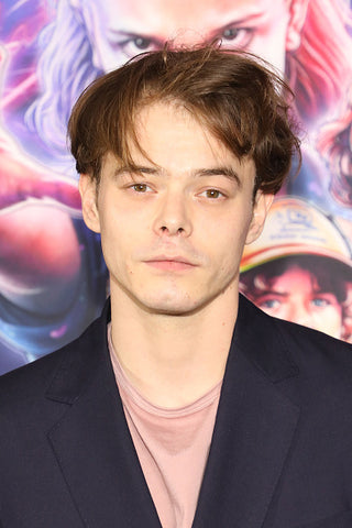 Actor Charlie Heaton with back board wearing blue jacket and pink tshirt