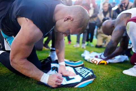 Christian McCaffrey signs jersey for fan big arms
