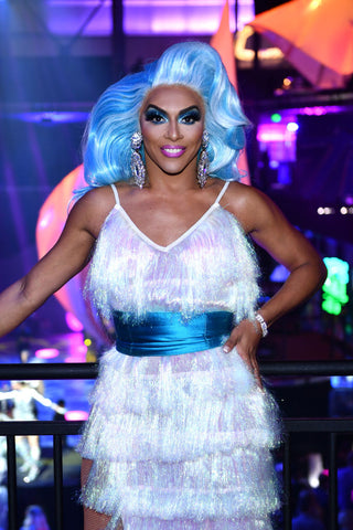Shangela in frilly white dress with blue wig and sash