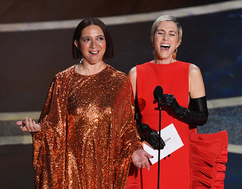 Kristen Wiig and Maya Rudolph on stage in gold dress and red dress
