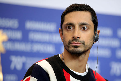 Brit Riz Ahmed on stage in black white and red top