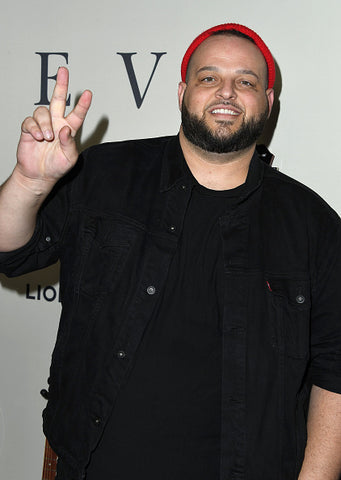 Daniel Franzese on red carpet in red hat and V sign