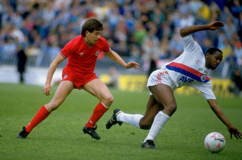 Andy Gray and Paul Hardyman tackle for the ball wearing retro football kits