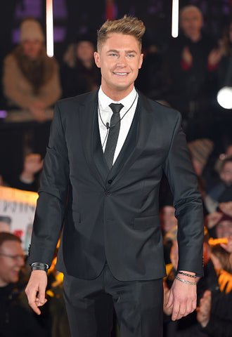 Scotty T wins celebrity big brother, London England. Wearing a black suit and tie.