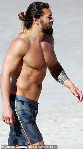Jason Momoa in profile walking on beach