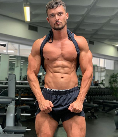 Box model flexes his muscles in black shorts