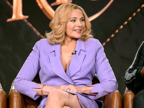 Kim Cattrall in violet jacket sat on stage