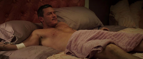 Luke Evans in bed naked covered in a sheet