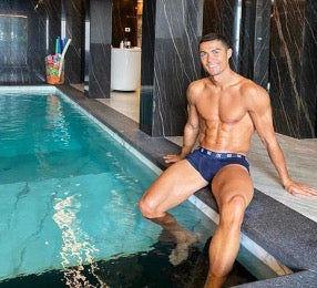 Cristiano Ronaldo sitting poolside showing off his bulging package through his tiny wet swim shorts, or are they his boxers? Whichever they are, we are a fan of anything wrapped so tightly around those chunky thigh muscles
