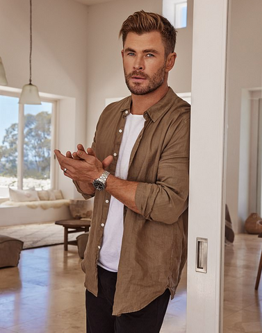 Chris Hemsworth leant against a doorway rubbing his hands together showing off his Tag watch