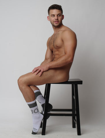 Josh Riquelme sat nude on a chair with just socks on