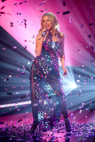 Kylie on stage in glitter and lighting pink and purple