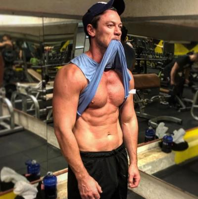 Luke Evans on instagram in the gym black cap and muscles blue vest