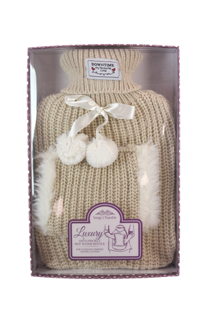 image of a boxed hot water bottle in a knited  cover with a pocket at the front for your hands. (cream in colour)