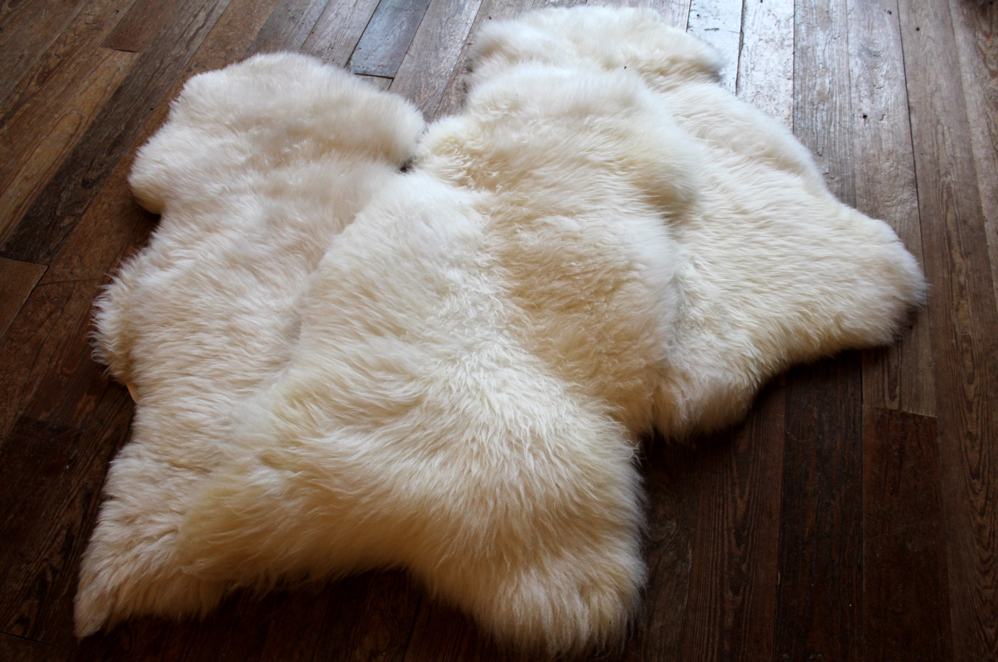 Three sheep skin rugs piled on a wooden floor