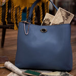 Francesca Stylish Italian Leather Handbag in light blue with postcards sticking out from the top.