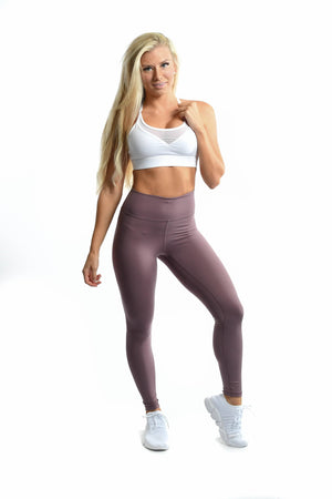 White sports bra and purple leggings