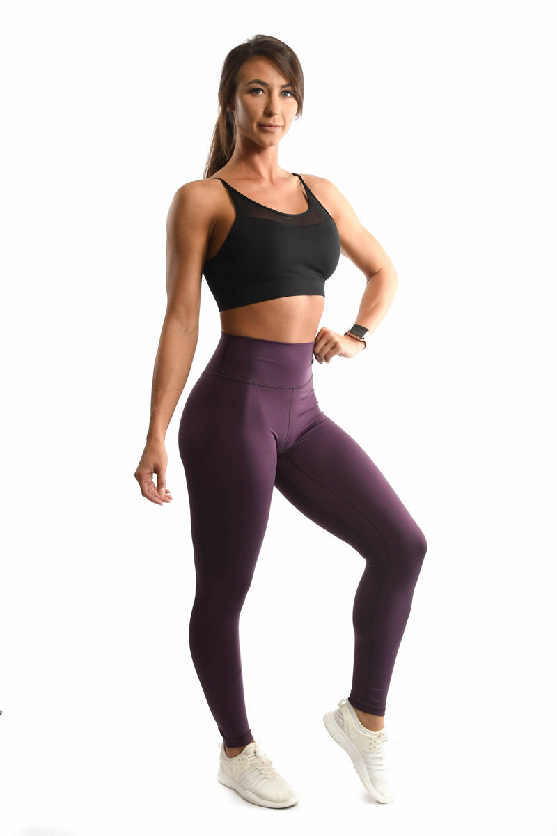 Purple leggings and black sports bra