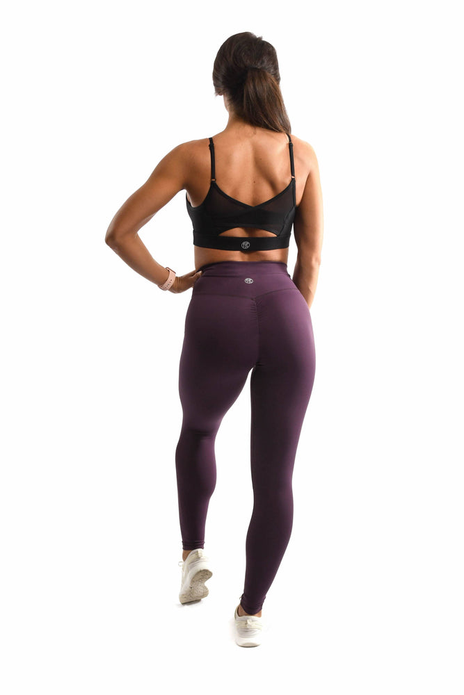 Back view of purple leggings and black sports bra