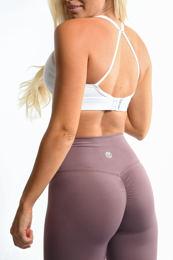 White sports bra straps and purple leggings
