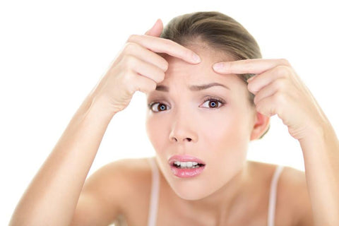 worried woman extracting pimples