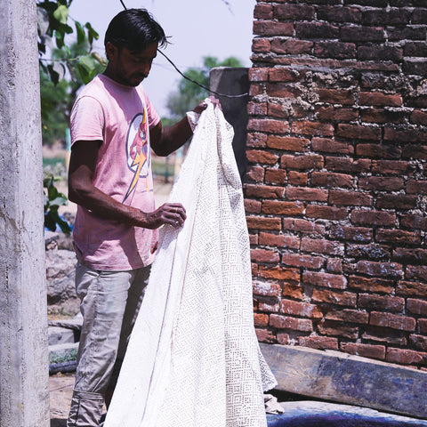 Artisan preparing to dip mud printed fabric in indigo vat