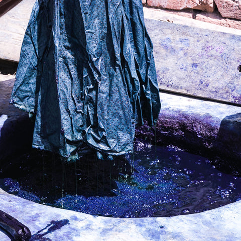 Artisan pulling out fabric from indigo vat