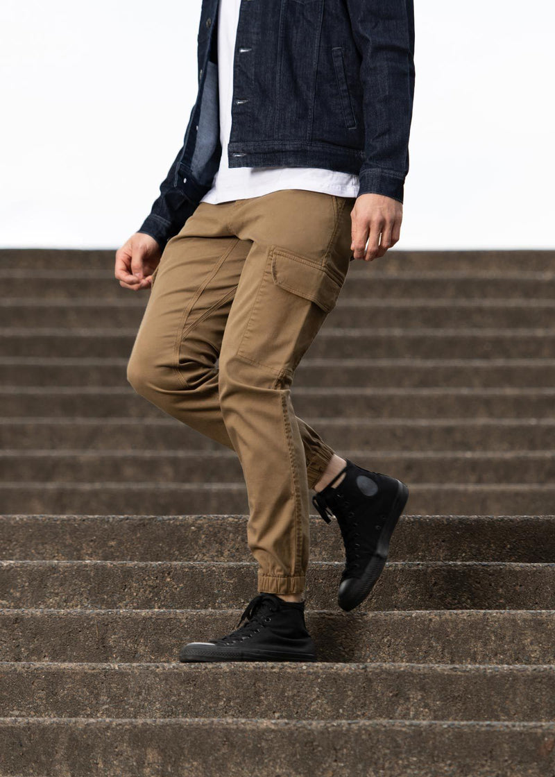 Man wearing brown athletic waterproof jogger pants walking down stairs