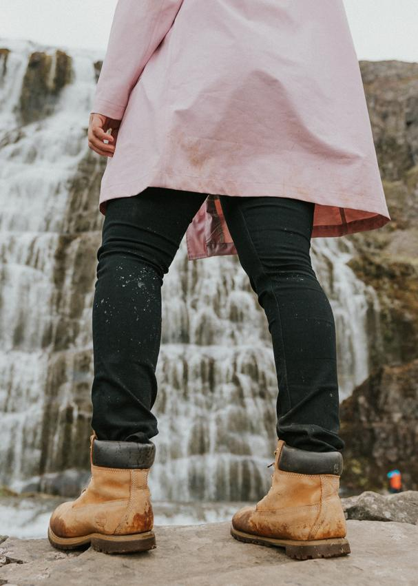 woman standing next to waterfall wearing water resistant black stretch jeans