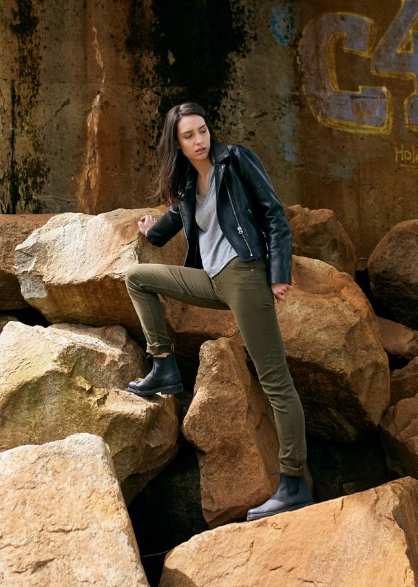 woman on rocks stretching in dark green dress pants