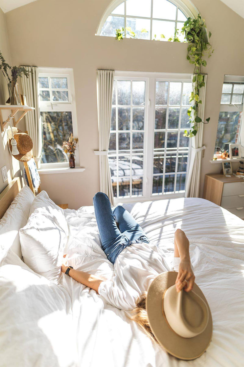 Woman wearing light wash high rise skinny jeans on bed
