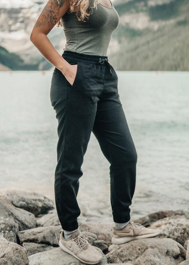 Woman near lake wearing black athletic joggers