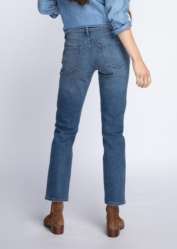 Woman wearing blue wash straight leg mid rise stretch jeans back