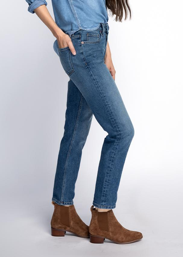 Woman wearing blue wash straight leg mid rise stretch jeans side