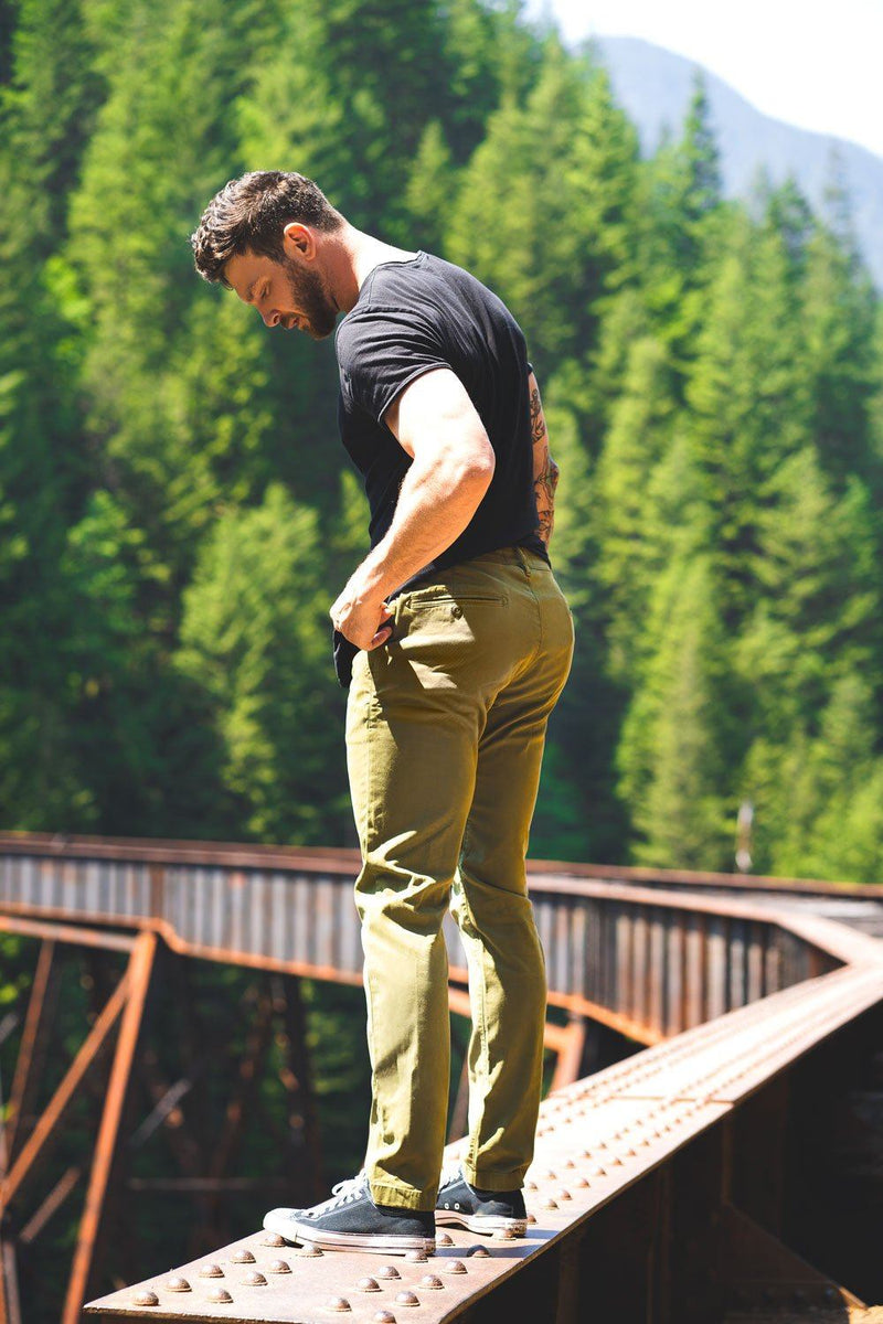 man standing on bridge in forest wearing green summer chinos