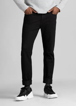 man wearing black slim fit waterproof stretch jeans front