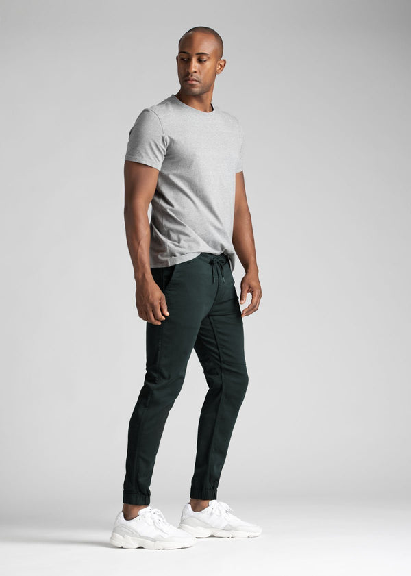 man wearing dark teal athletic joggers full body