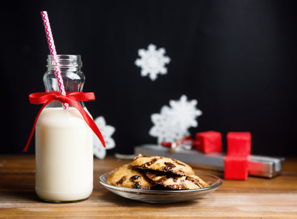 a glass of milk and a plate of chocolate chip cookies being left out for Santa Claus