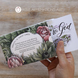 "Back of Identity in Christ open card pack with partially protruding floral card emerging from the open box held in a right hand. There are floral illustrations on the box and a blurb that reads ""Identity in Christ Cards. 30 Bible verse art cards affirming your identity as a dearly beloved child of God. Start living from a place of freedom and security in Jesus today! Art & Design by Emma Davis copyright 2020 Bible Affirmations Art."""