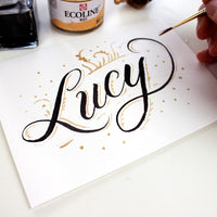 "Handwritten card with script ""Lucy"" handlettered with black and gold ink and hand holding a round watercolor brush"