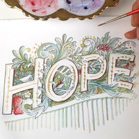 Artist's hand holding a paintbrush with paint palette next to completed HOPE watercolour illustration with strawberries, grapes, and leaves surrounding the word