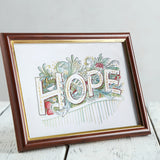 Mocked up frame of A5 HOPE drawing in a brown frame on a table