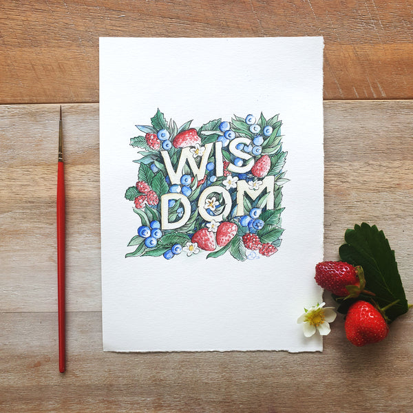 Styled photo of illustration of the word wisdom picturing the original artwork with real strawberries and a paint brush on a wooden background