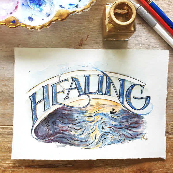 Original A5 painting of the word Healing arching in a banner over an illustrated water scene with a little boat sailing into the golden horizon. Styled on a wooden background with watercolour palette and gold ink pot