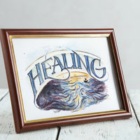 Stylised mockup of Healing drawing in a brown wooden frame on a minimalist white table.