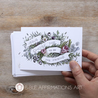 "Hand holding postcard with floral illustration with banner reading ""Jesus chose me to be his friend."" Bible Affirmations Art logo with Lamb icon"