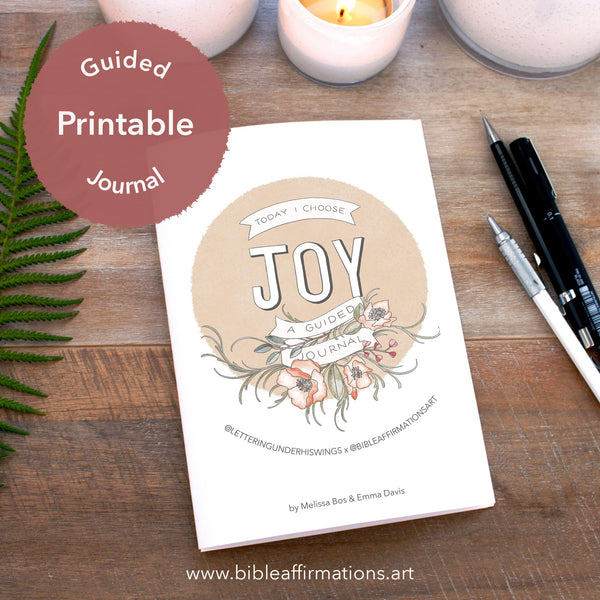 Printed Joy Journal booklet on wooden desk arranged with fern leaf, candles & pencils