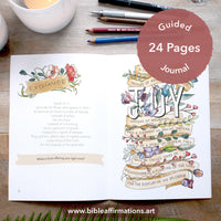 Printed A5 booklet Joy Journal open to page 8 on a wooden desk styled with candles, fern leaf, and stationery